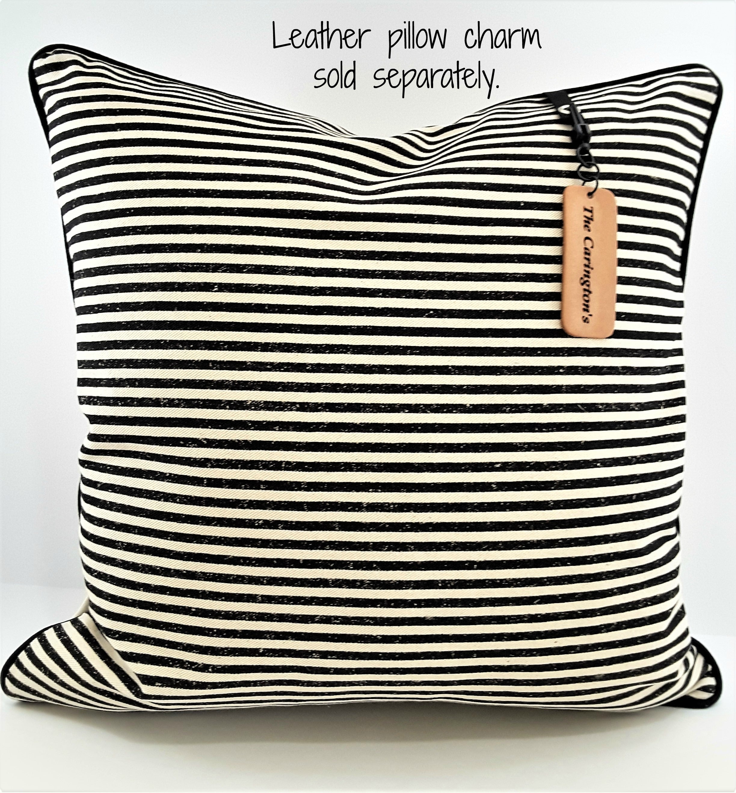 LEATHER PILLOW TAG HANGING FROM HORIZONTAL STRIPE PILLOW