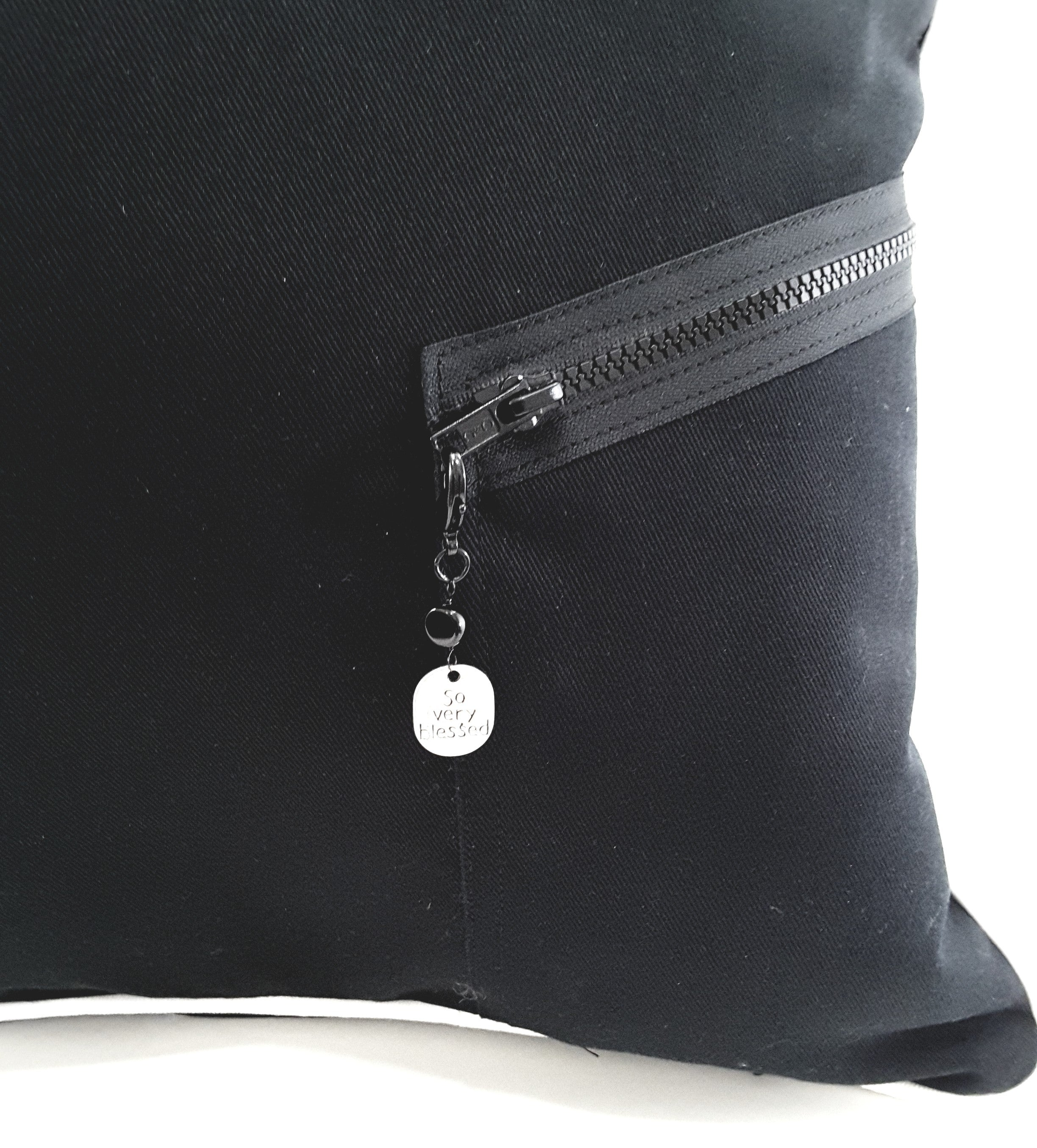 closeup of black zipper with charm on black denim pillow
