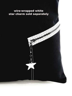 closeup of white polka dot zipper with white star charm on black denim pillow