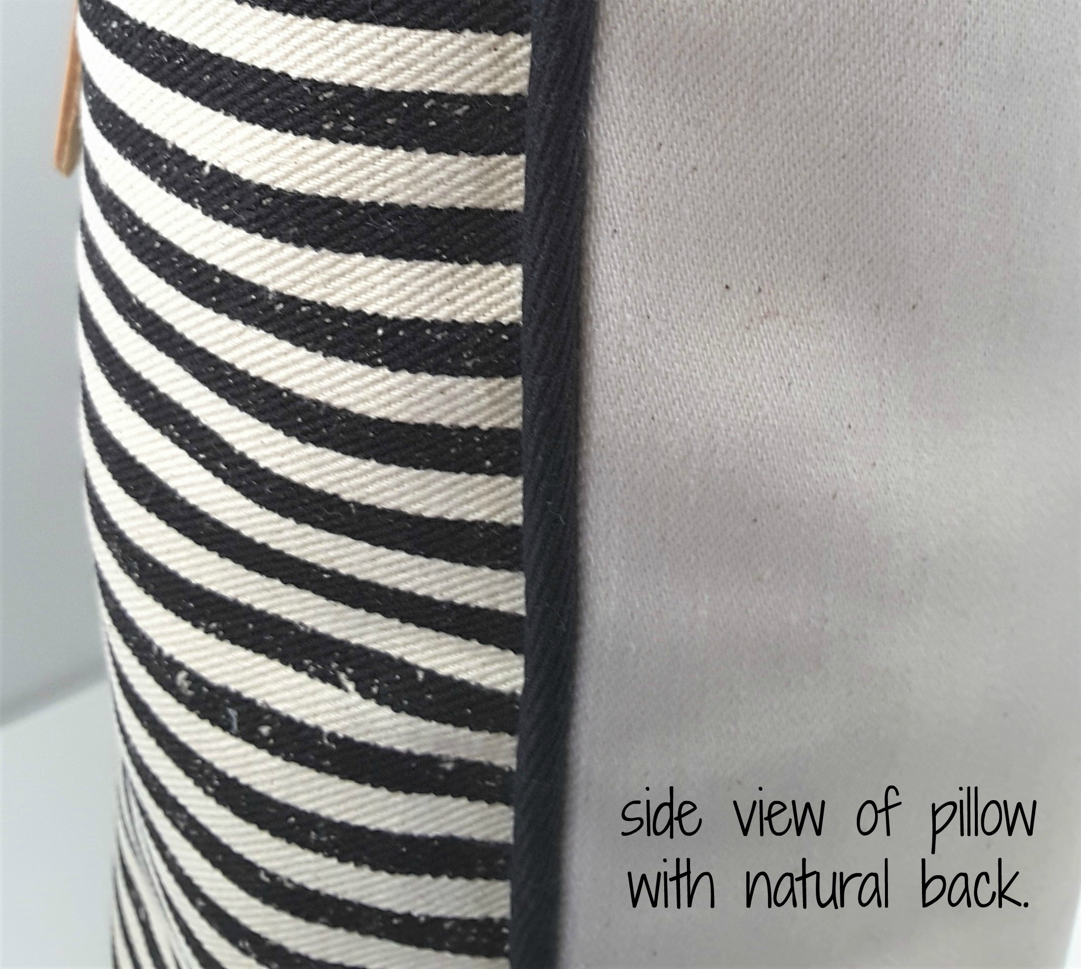 Side view of black and natural stripe pillow with natural denim back