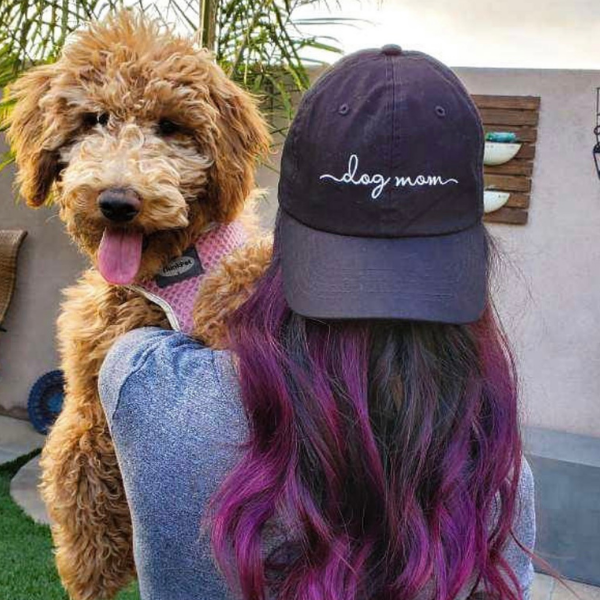 black dog mom baseball hat worn backwards by a female with purple hair carrying a big brown dog