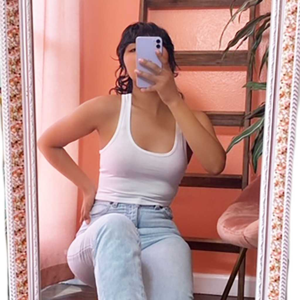 female in front of a mirror tanking a selfie with a white Racerback crop tank top and denim jeans-DSY Lifestyle