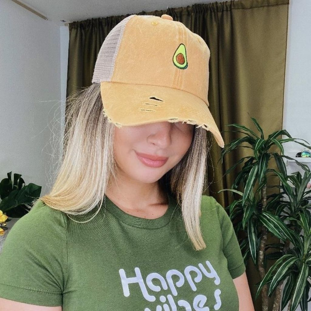 Female wearing a yellow trucker hat embroidered with a avocado - DSY Lifestyle