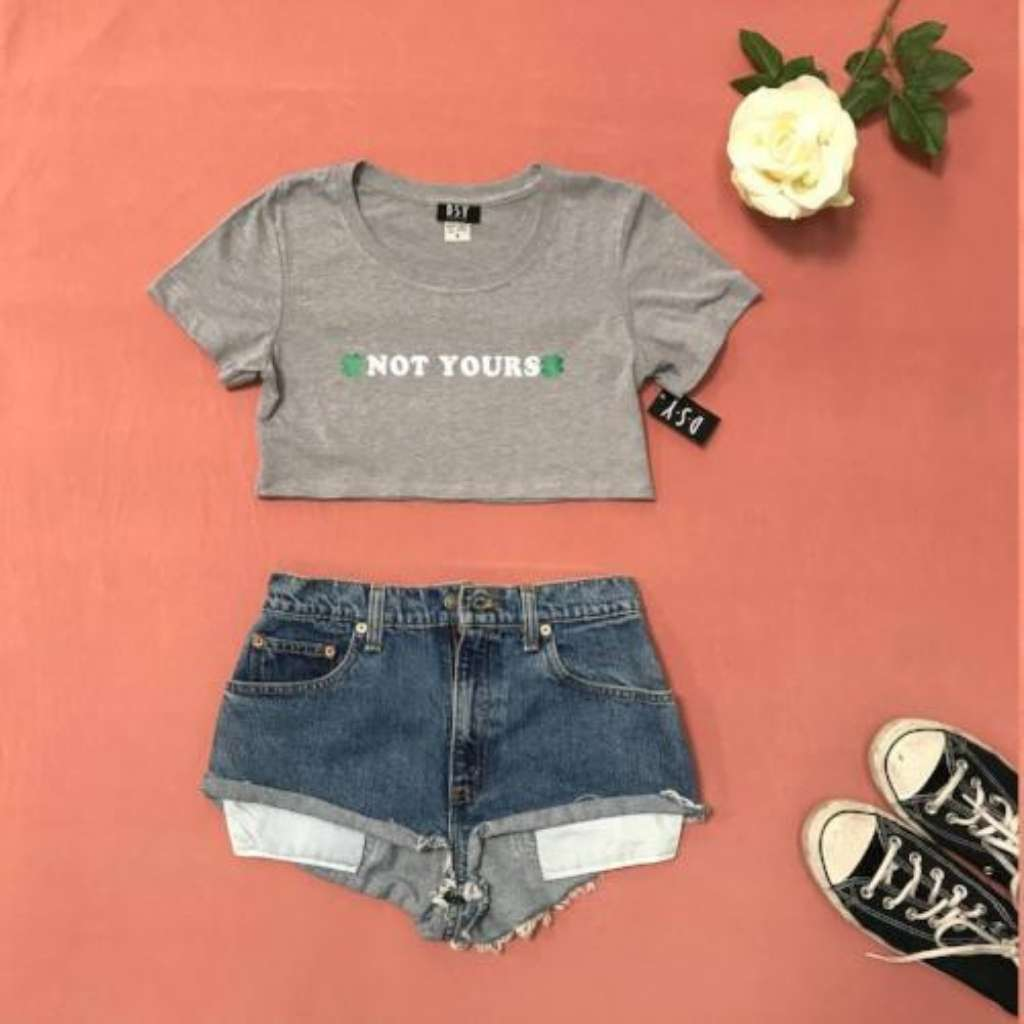 Flat lay of heather grey crop top with not yours printed on the front paired with jean shorts and sneakers - DSY Lifestyle