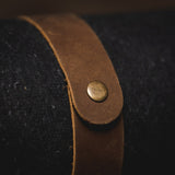 Savage Gentleman brown leather strap around wool blanket.