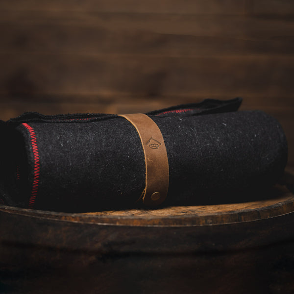 Savage Gentleman wool blanket with red stitching and leather strap.