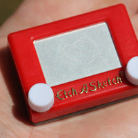 World's Smallest Etch A Sketch in hand