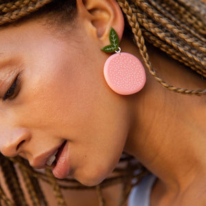 Large Acrylic Grapefruit Earrings on a model by WOLL