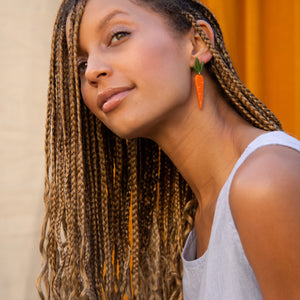 small carrot earrings on model with braids