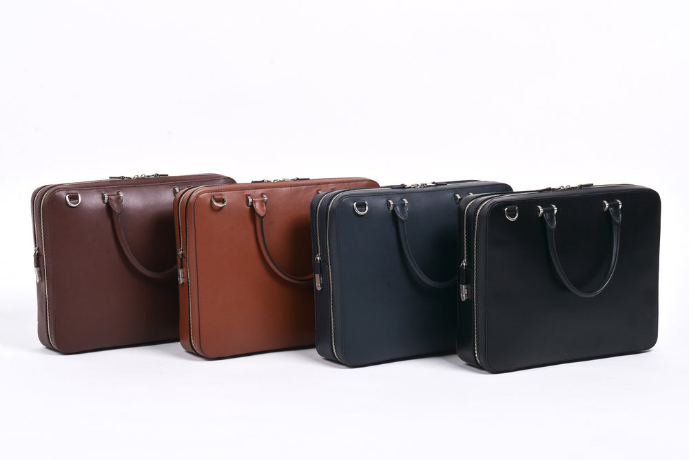 Bond Travel Briefcase in Smooth Veg Tan Cowhide (L to R): Dark Brown, Tan, Navy, Black