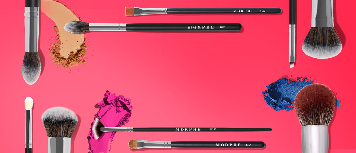 Morphe brushes on a pink background with makeup swatches
