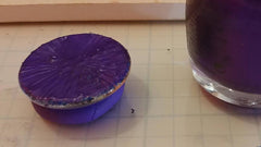 Glass cabochon with a layer of dark shiny purple added over the entire surface