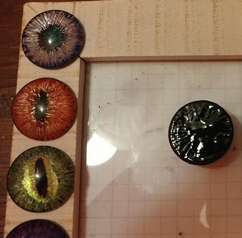 Glass cabochon with a layer of black applied over the entire surface and previously completed dragon eyes next to it