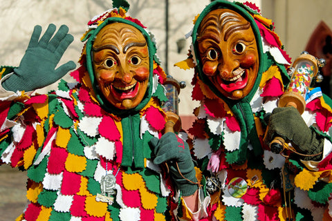 two people wearing masks of distorted human faces with colorful festive costumes