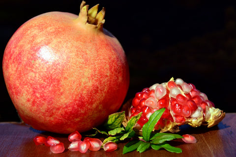 image of a whole pomegranate and a partial pomegranate with a pile of ripe pomegranate seeds