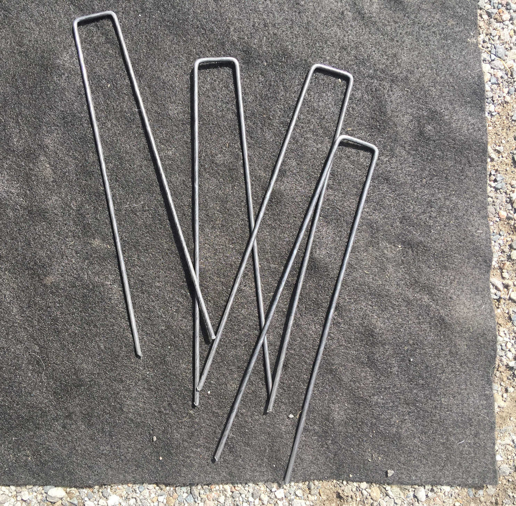 9-inch sod staples laying on a piece of black cloth