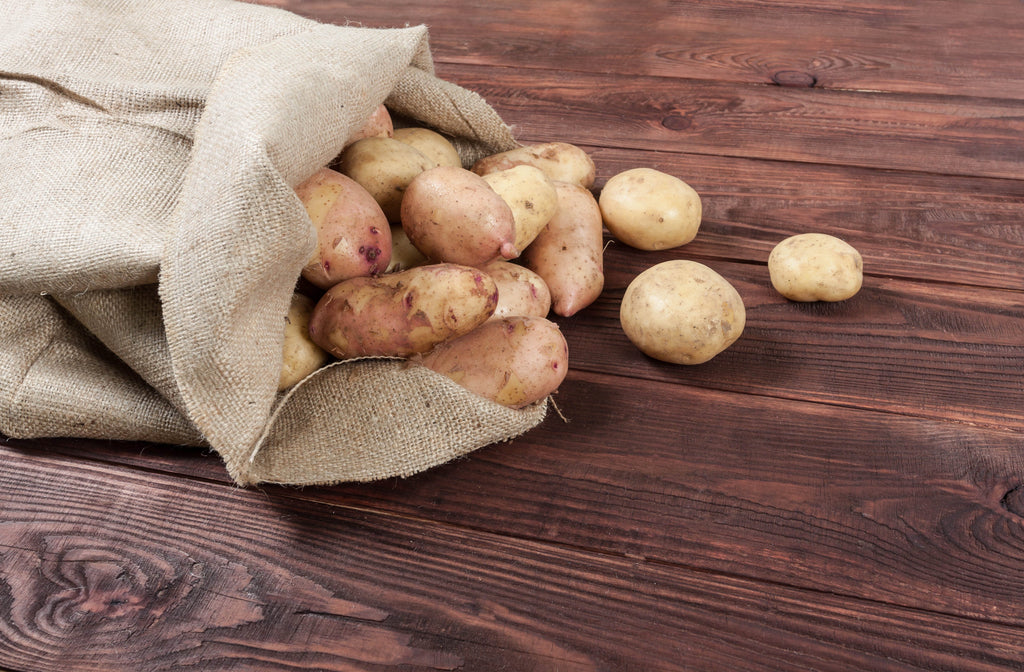 Burlap bag with potatoes inside flowing out