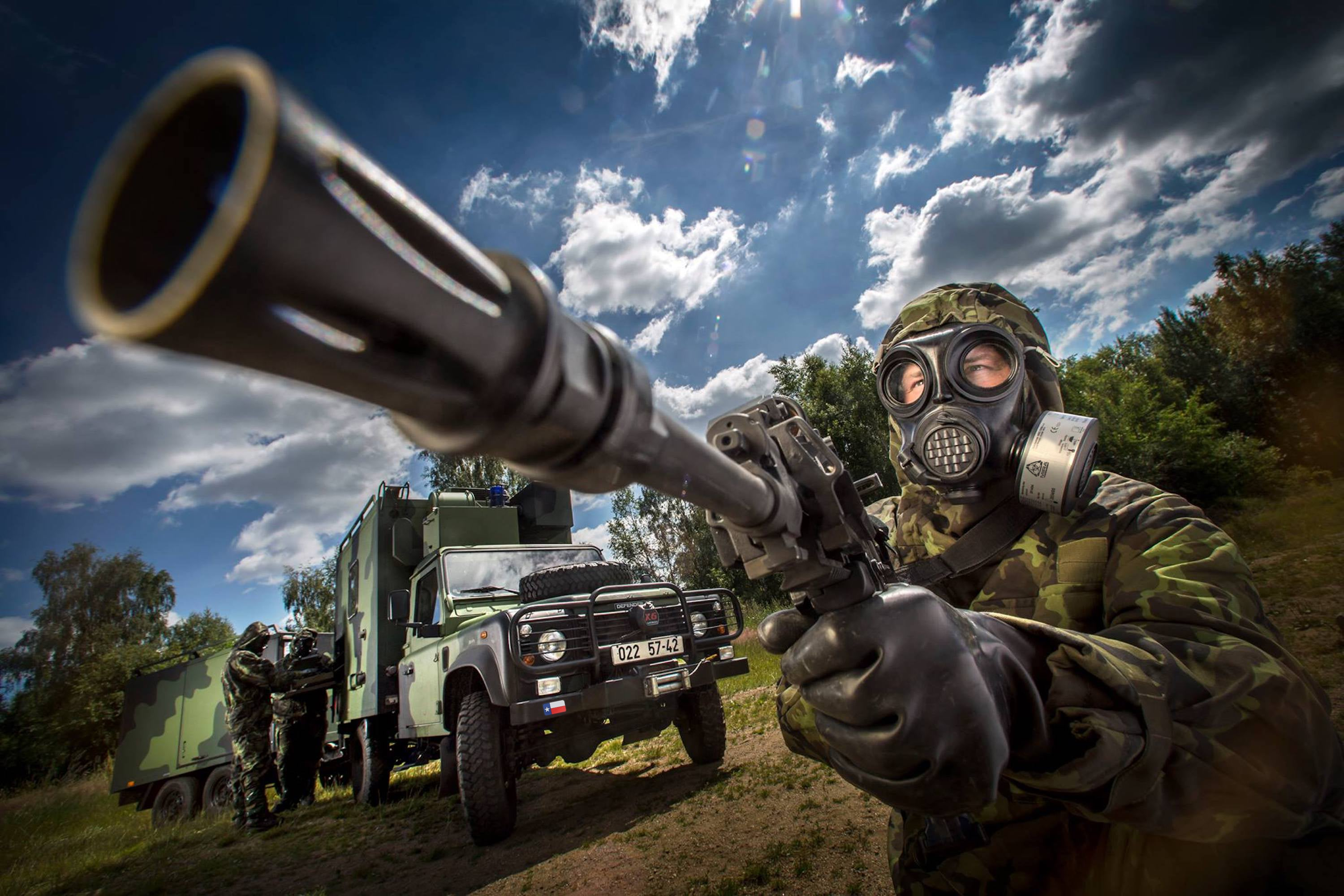 Solider using the NBC-77 SOF CBRN gas mask filter with a firearm