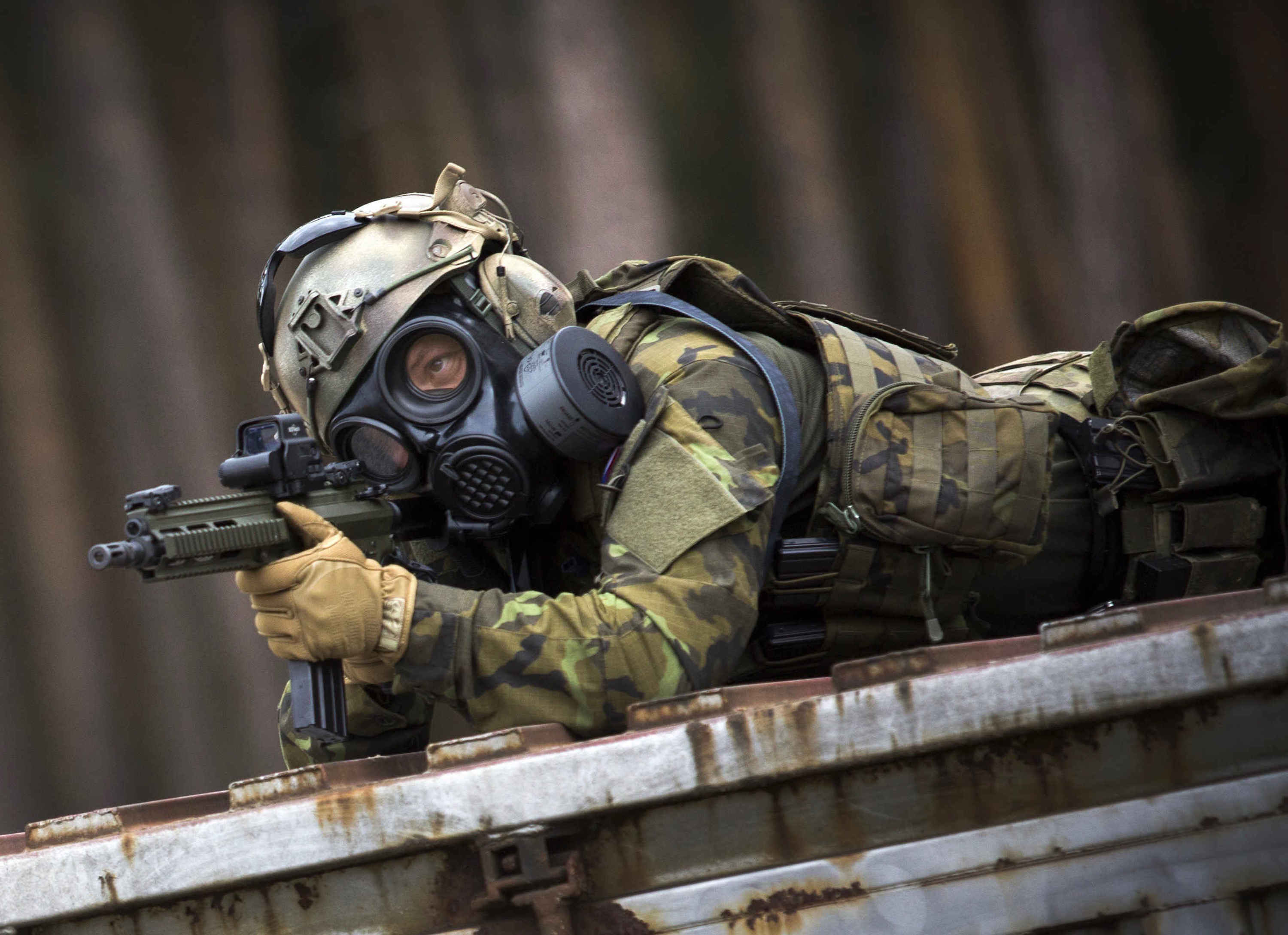 Soldier laying down while aiming through a rifle, while wearing the CM-7M military mask