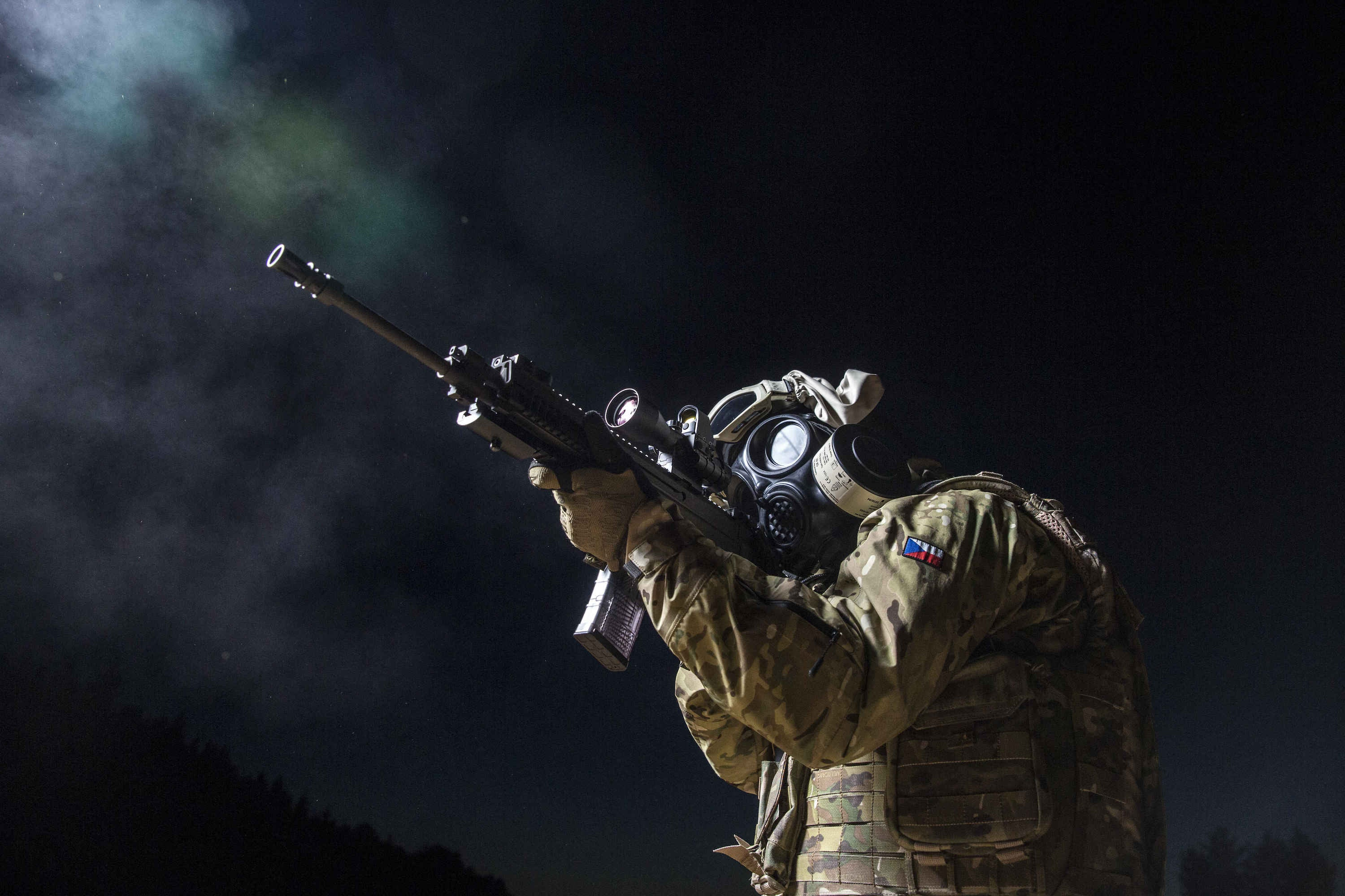 Soldier aiming down his rifle sights while wearing the MIRA Safety CM-7M military gas mask
