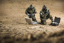 Two soldiers testing ground samples with the CM-7M warfare mask