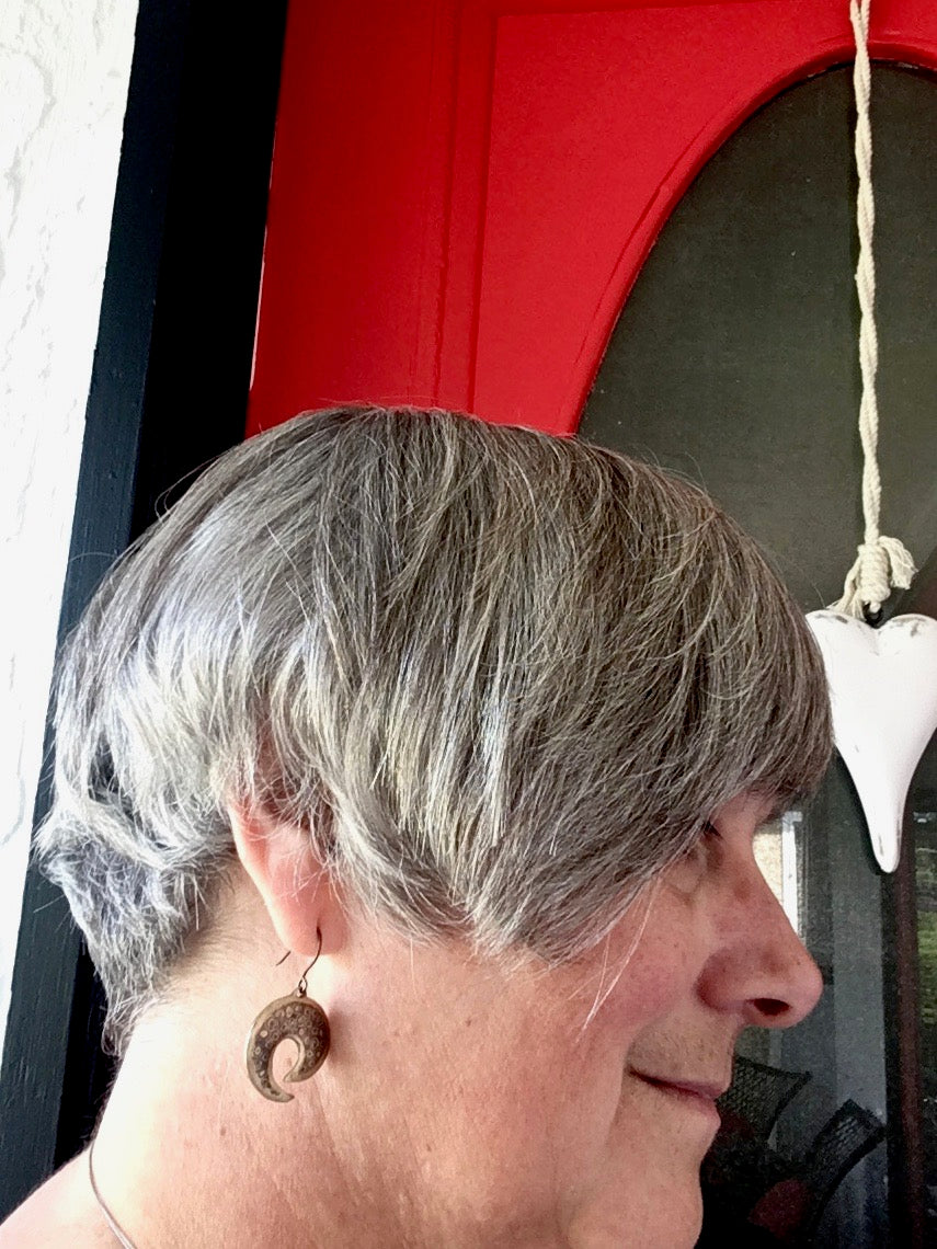 Patterned metal earrings in front of the red door