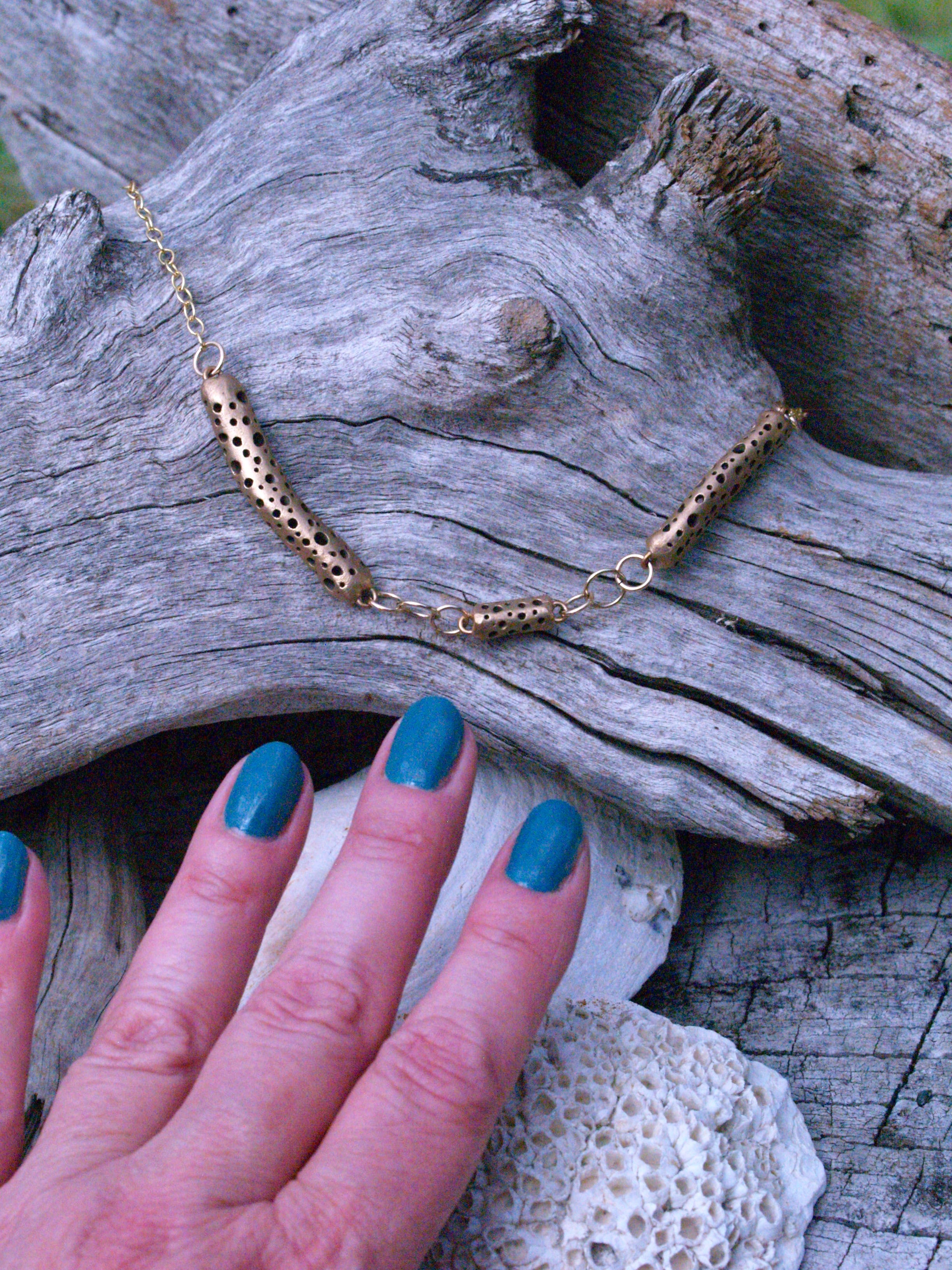 Reaching for the kelpie wearing a bronze art jewelry necklace