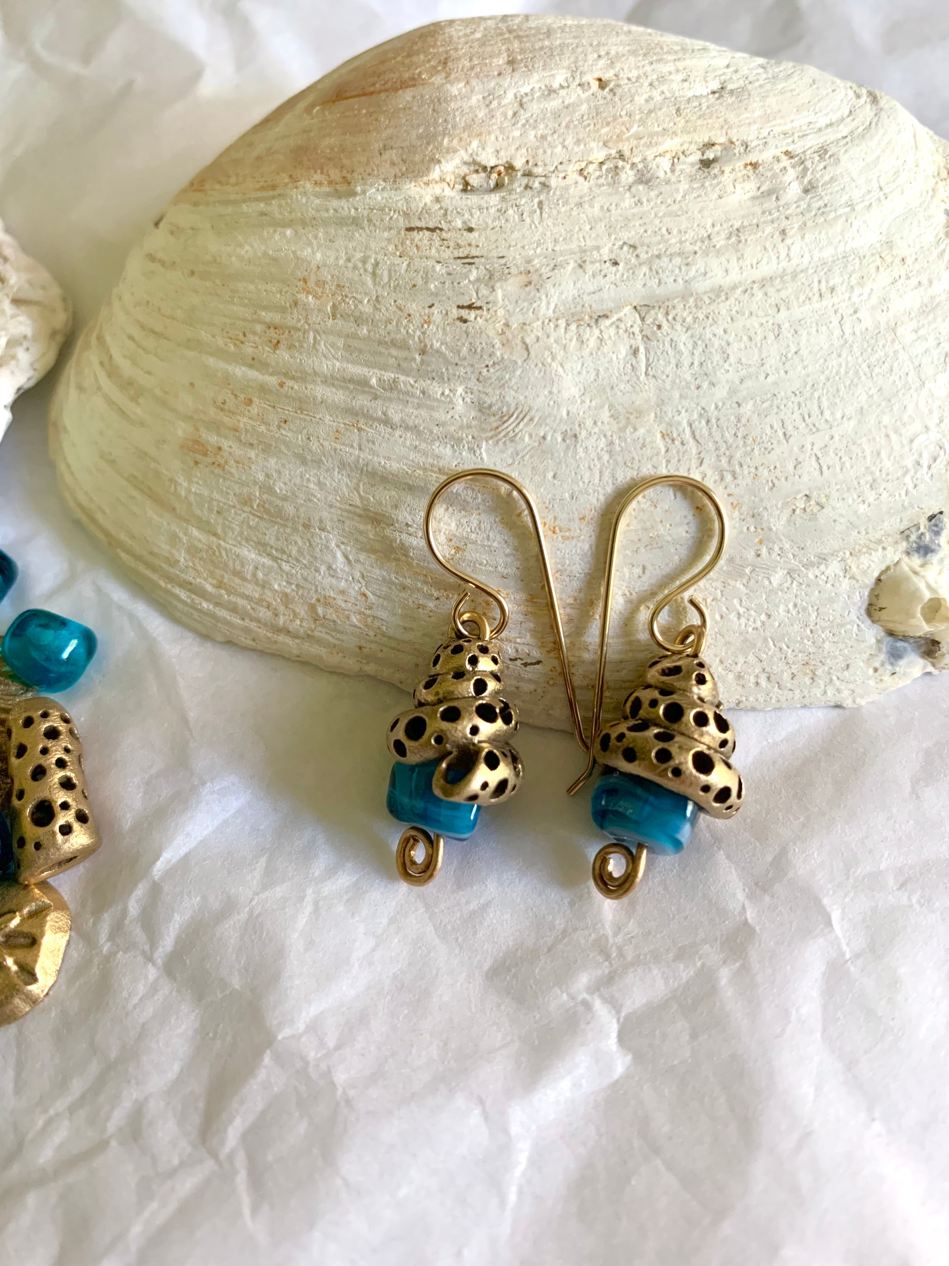 Shell inspired bronze earrings with blue artisan made glass beads