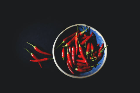 Bowl of red chillies on black background taken from above