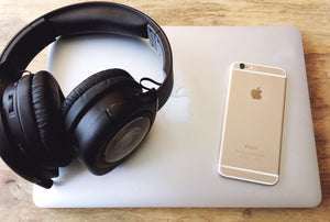 Headphones iphone and laptop on coffee table