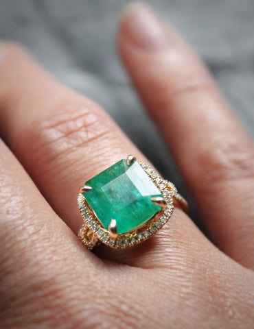 Emerald and Diamond ring on finger of Sea and Stone jewelry founder