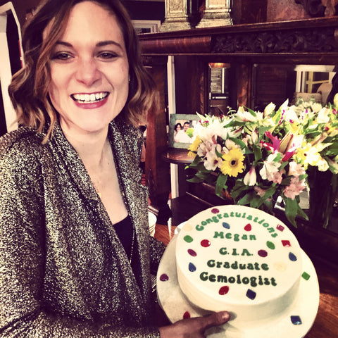 Sea and Stone founder Megan Connelley holding a cake to celebrate becoming a GIA Graduate Gemologist
