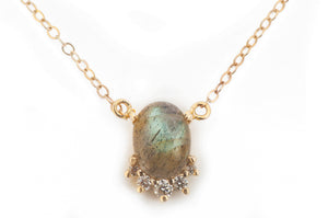 Sea and Stone Jewelry -  A labradorite cabochon pendant, set in 14 karat yellow gold with a curve of four diamonds underneath, hangs from a gold chain necklace. close up.