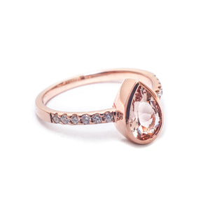 Sea and Stone Jewelry - A pear shaped blush morganite stone set in a rose gold ring with diamonds studding the band.