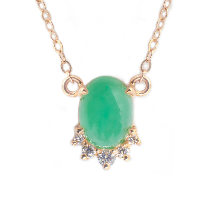 Sea and Stone Jewelry -  A chrysoprase cabochon pendant, set in 14 karat yellow gold with a curve of four diamonds underneath, hangs from a gold chain necklace. close up.