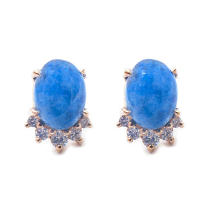 Sea and Stone Jewelry -  Stud earrings featuring lapis lazuli cabochons set in 14 karat yellow gold with a curve of four diamonds underneath. Pale denim blue lapis shown. Close up.
