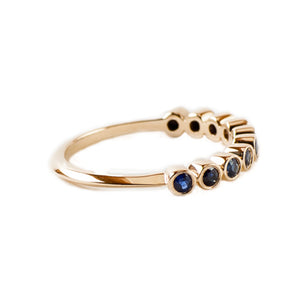 Sea and Stone Jewelry - Bezel ring with 2 millimeter faceted round sapphire stones set in 14 karat yellow gold. September birthstone. Side view.