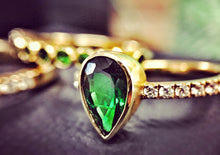 Sea and Stone Jewelry - A pear shaped faceted Tsavorite, beautiful emerald colored garnet, stone set in a yellow 14 karat gold ring with diamonds studding the band. Close up.