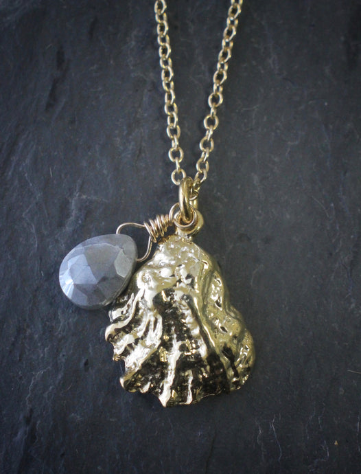 Sea and Stone Jewelry -  A dainty gold vermeil oyster shell pendant, embellished with a corundum-sapphire briolette,  hangs from a gold vermeil chain necklace with a lobster clasp.