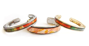 Sea and Stone Jewelry - Cuff bracelets with leather inlayed on gold or silver plated metal. Shown in thick and thin sizes.
