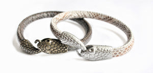 Sea and Stone Jewelry - A cuff bracelet in the shape of an Ouroboros, or a snake biting it's own tail. Both color options shown: Dark Grey-bronze and White - Rose.