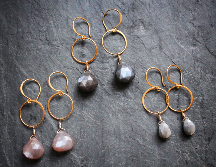 Sea and Stone Jewelry - Drop earrings featuring circlets over dangling, hand wrapped, teardrop shaped moonstone cabochons with gold vermeil hook ear wires. Three colors shown: mauve, dark grey, and light cool grey.