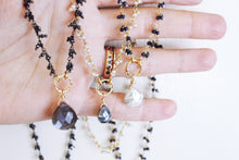 Sea and Stone Jewelry - Dainty gemstone necklaces in gold plated or blackened sterling silver, with a fringe of tiny gemstones down the chain and a large gemstone pendant, draped over a hand