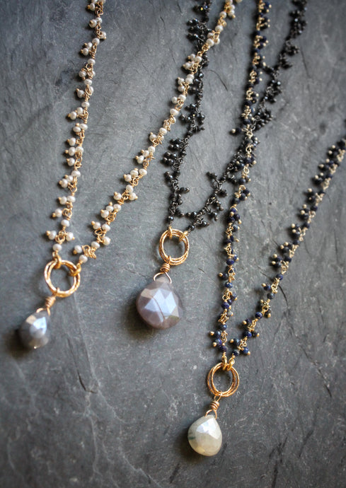 Sea and Stone Jewelry - Dainty gemstone necklaces in gold plated or blackened sterling silver, with a fringe of tiny gemstones down the chain and a large gemstone pendant. Gemstone combinations: Pearls and blue gray moonstone. Lapis and white Corundum. or black spinel and mauve moonstone.