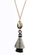 Sea and Stone Jewelry - Two genuine horsehair tassels, grey and black, hang from a faceted, bezel set, pyrite stone pendant on a gold necklace.