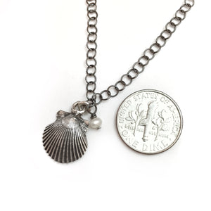 Sea and Stone Jewelry - A dainty silver shell pendant, hand crafted from shells found along Florida's gulf coast, embellished with a tiny pearl, hangs from a blackened silver circle link necklace. Shown with a dime for size reference.