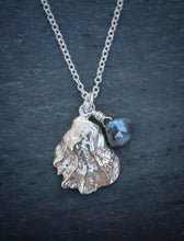 Sea and Stone Jewelry -  A dainty sterling silver oyster shell pendant, embellished with a corundum-sapphire briolette,  hangs from a silver chain necklace with a lobster clasp.