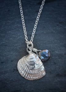 Sea and Stone Jewelry -  A dainty sterling silver cross barred venus shell pendant, embellished with a corundum-sapphire briolette,  hangs from a silver necklace with a lobster clasp.