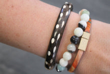 Sea and Stone Jewelry - Bangle bracelets made of natural buffalo horn. Color is dark with light contrast. Displayed being worn with other bracelets.