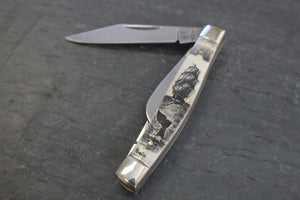 A pocket knife with three blades that nestle into a compact scrimshaw handle made of ethically sourced bone, with an artfully etched Ship and whale tail design.
